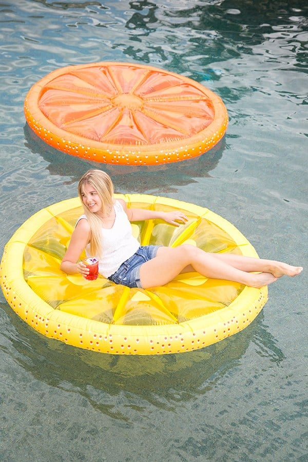 Girl floating on a lemon slice pol float at a pool party