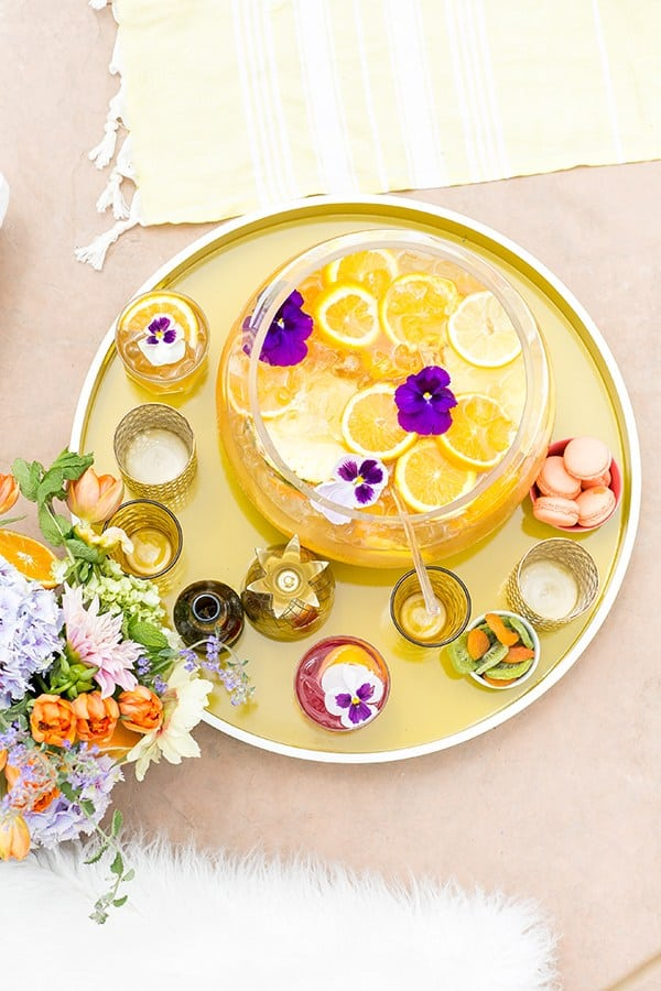 Pineapple party punch in bowl with orange slices on a yellow tray with flowers and pretty summer cups.
