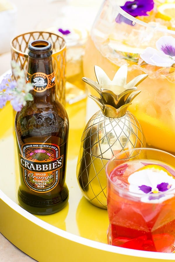 Crabbies ginger beer with a gold pineapple shaker and a cocktail on a yellow acrylic tray.
