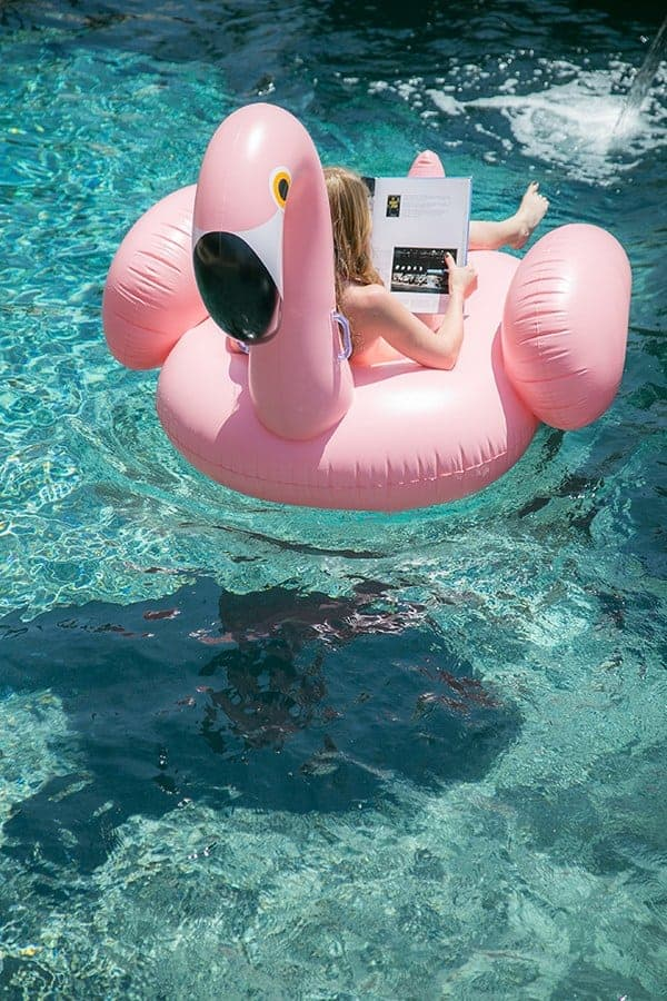 girl on a pink flamingo pool float reading a book