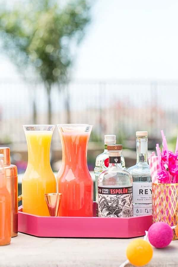 Cocktail station with juice, spirits on a pink tray.