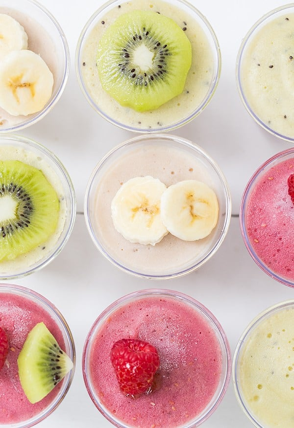 Colorful nice cream in plastic cups with bananas and raspberries and kiwis on them