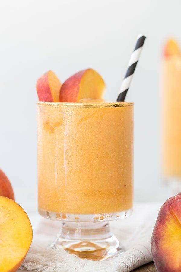 Frozen peach Bellini with a black straw.