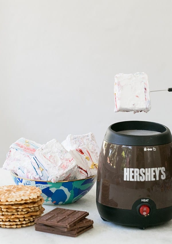Giant marshmallows with red and blue in a bowl with a Hershey's indoor toaster.