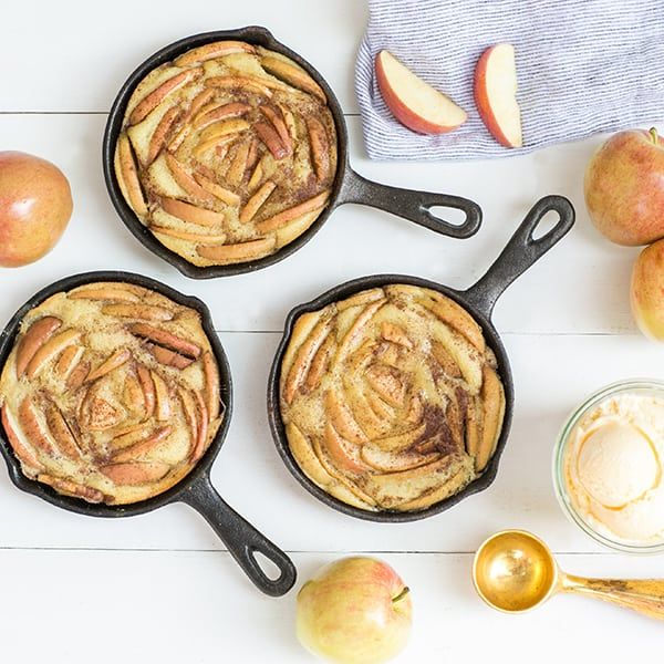 top down shot of 3 olive oil cakes with sliced apples on the side