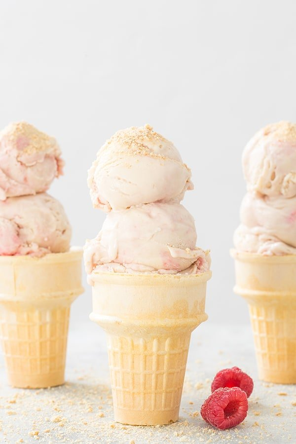 There ice cream cones with raspberry swirl cheesecake ice cream