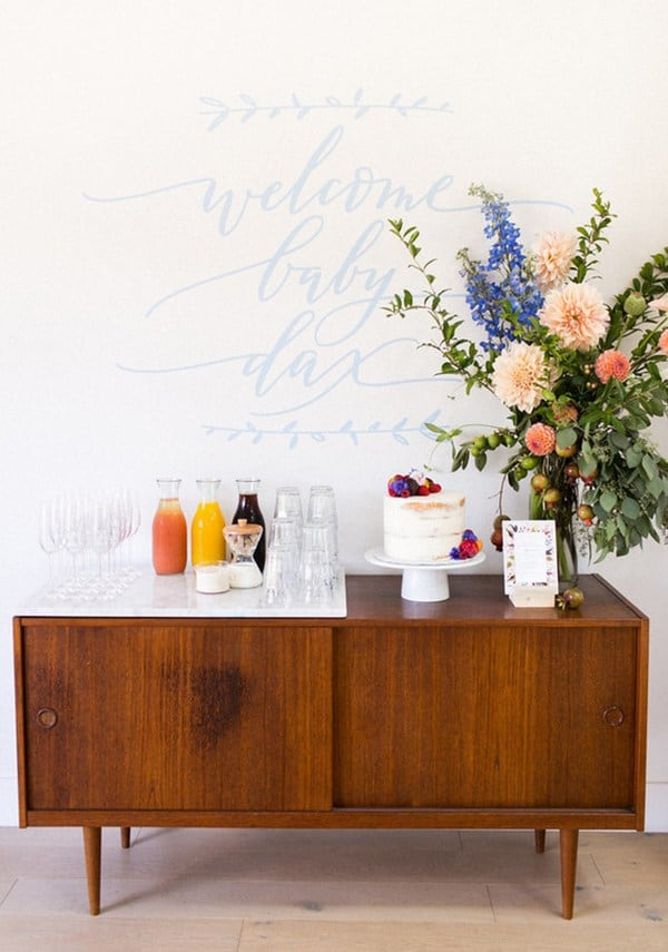 Flowers and drinks and a cake on a modern bar.