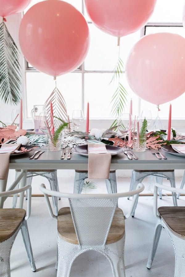 Large pink balloons with ferns over a place setting for a Tropical Baby Shower