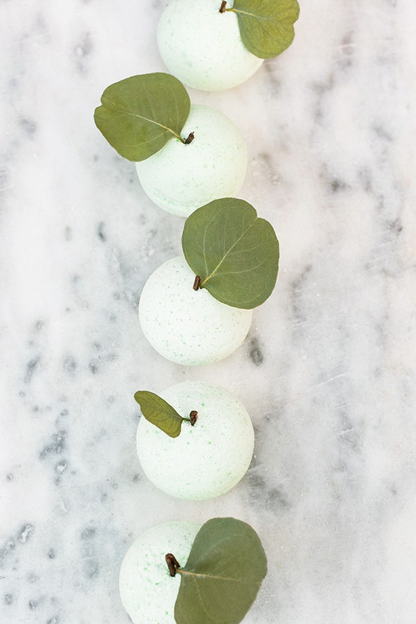 green apple bath bombs in a row on marble