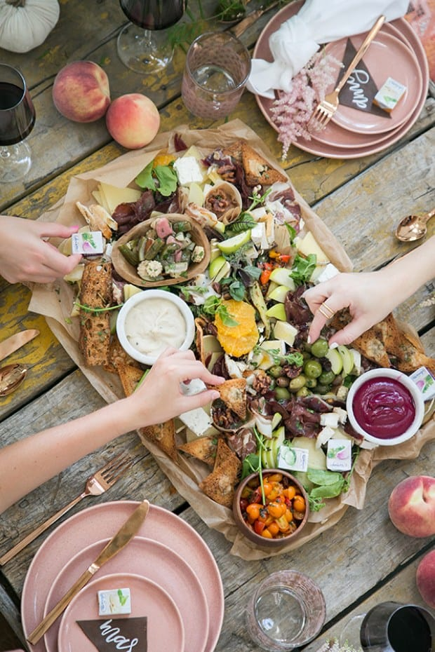 hands reaching for food on the charcuterie platter