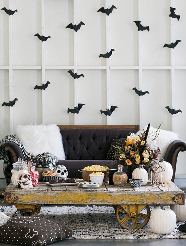 Halloween set-up with black couch, bats on the wall and  rustic table.