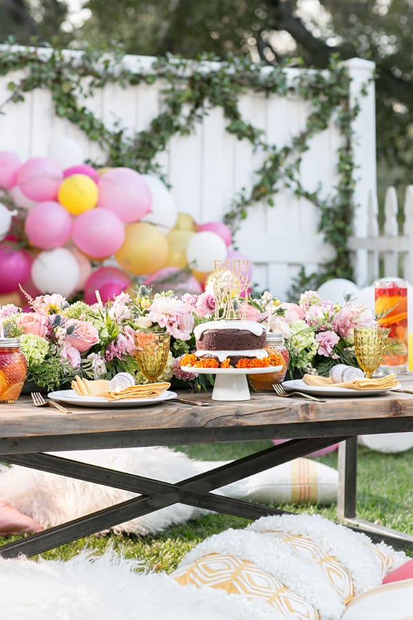 Gluten free birthday party setting with cake, flowers and balloons.