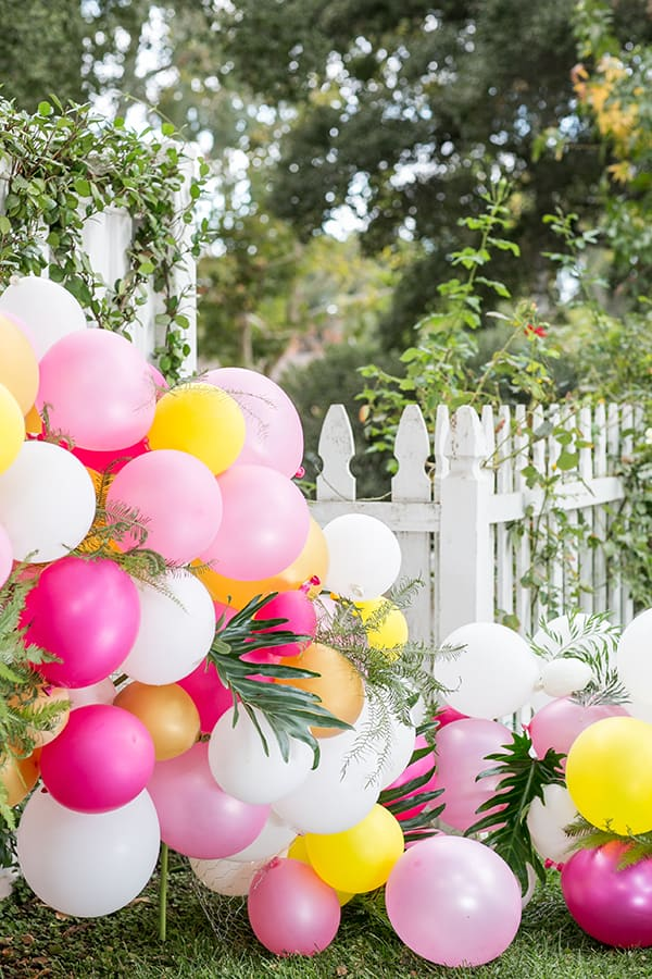 Balloon arch outside white fence.