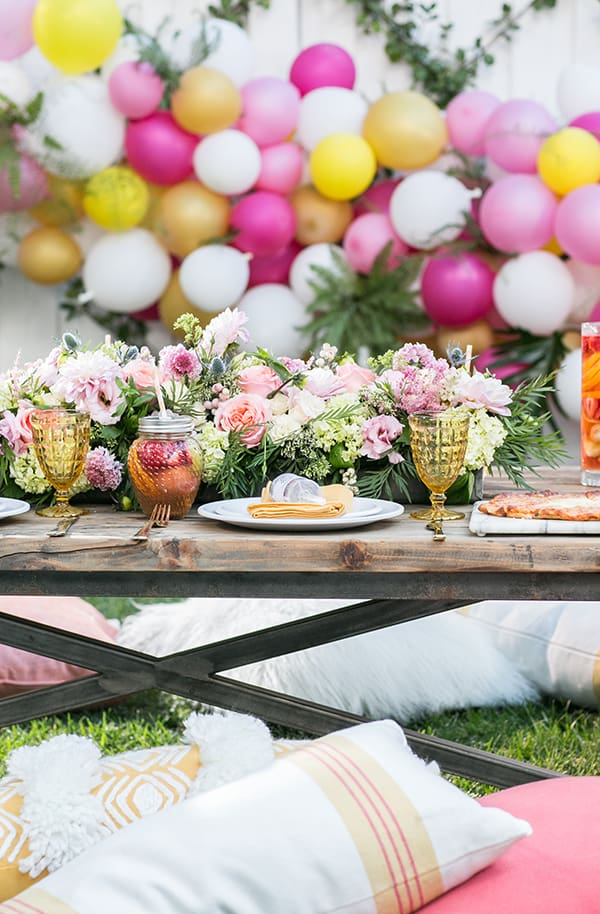 Birthday party setting with balloons and a low wooden table with flowers and throw pillows.