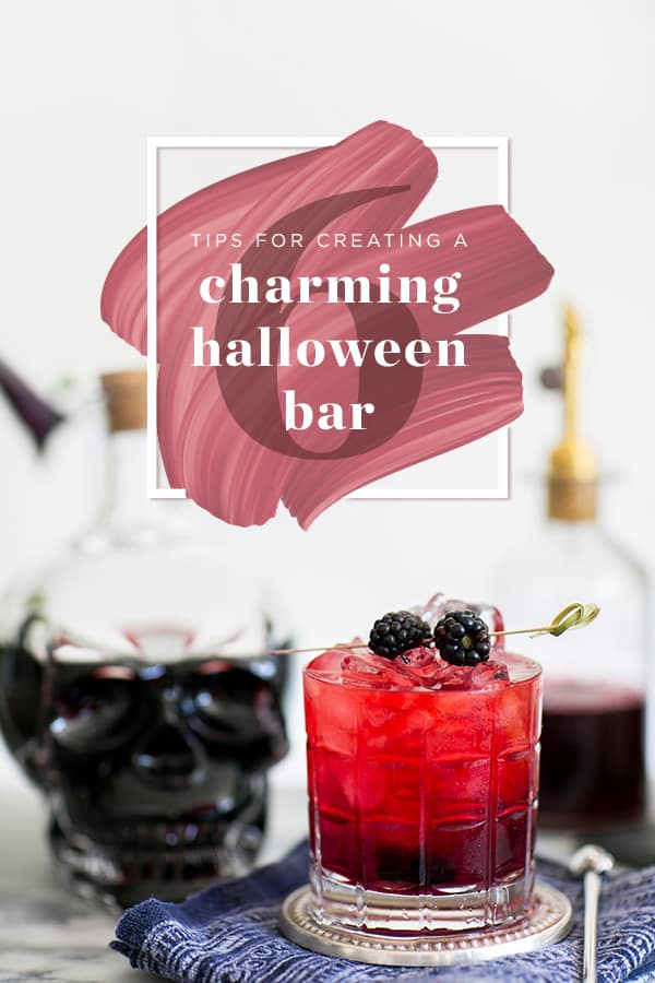 Red cocktail with blackberries and a Halloween skull.