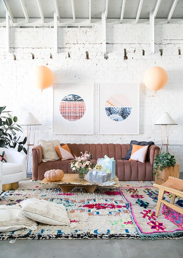 Fall baby shower decoration with pink couch and colorful rug.