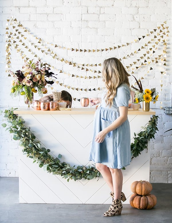 Eden Passante standing in front of a white bar at her fall baby shower.