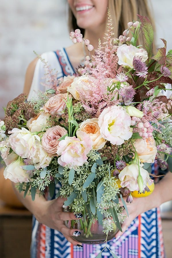 Girl holding a giant vase of fall flowers