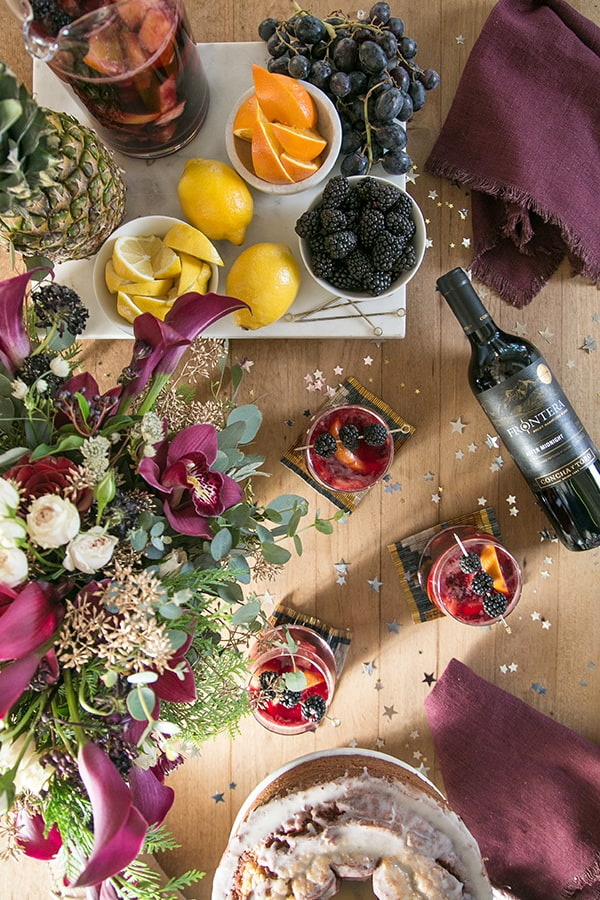 Overhead picture of fruit on a bar, wine bottle and glass of sangria
