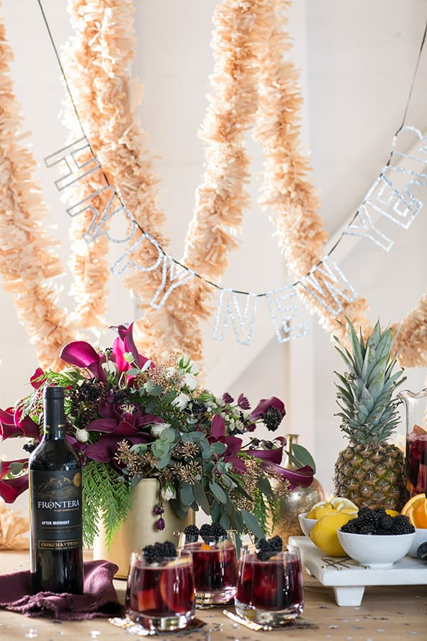 Sangria in glasses with a bottle of sangria and flowers. Garland and a happy new year sign draped over.