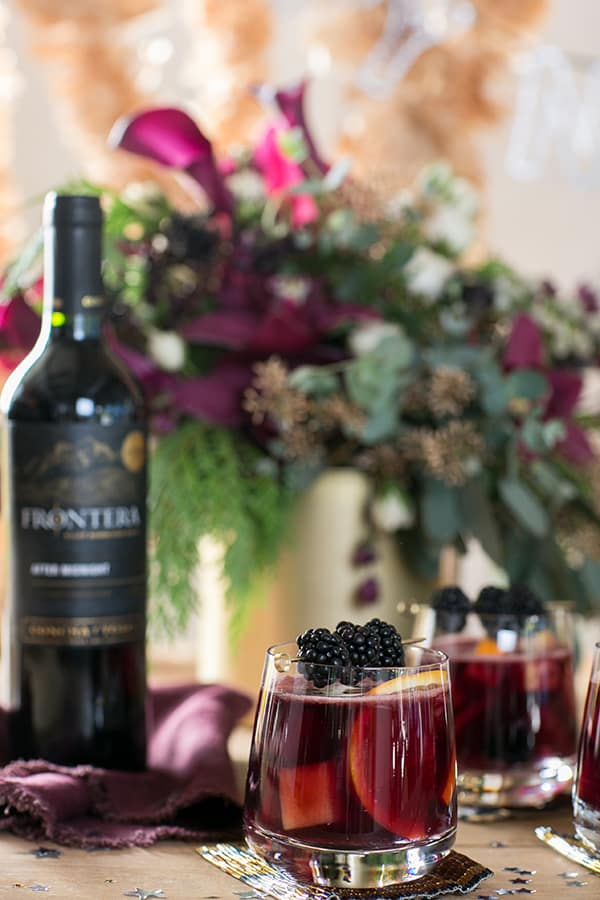 Glass of red sangria with blackberries on a table with a bottle of red wine.