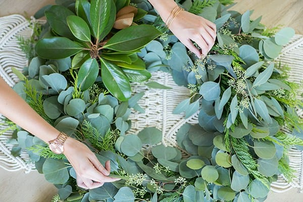 hands assembling a wreath
