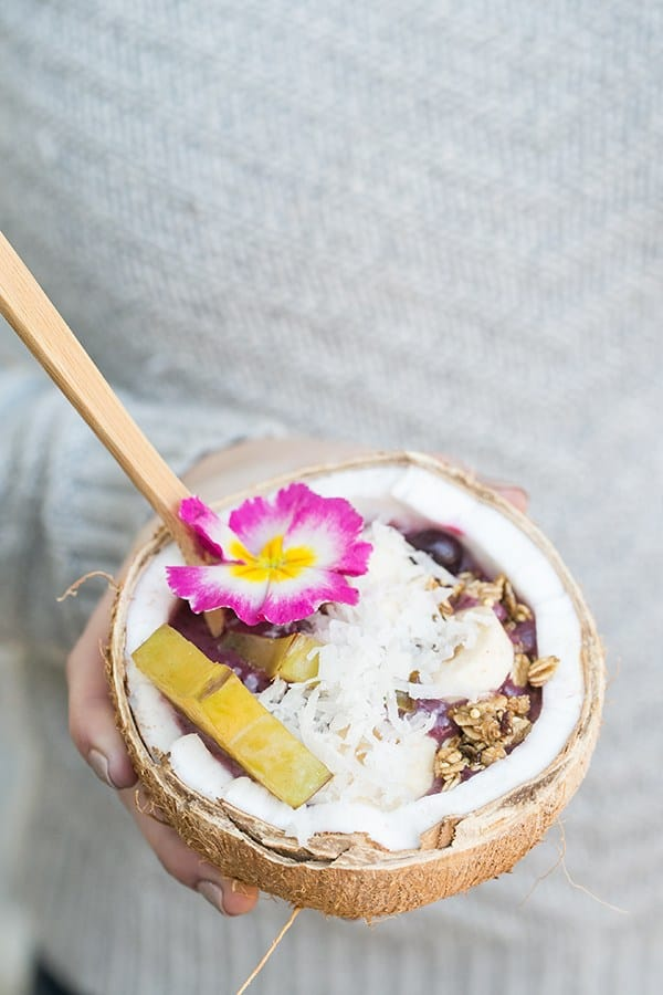 Holding an acai bowl in a coconut with shredded coconut, starfruit and an edible flower.