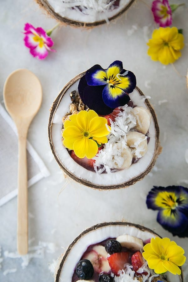 Acai bowls in coconuts with sliced bananas, edible flowers and shredded coconut.