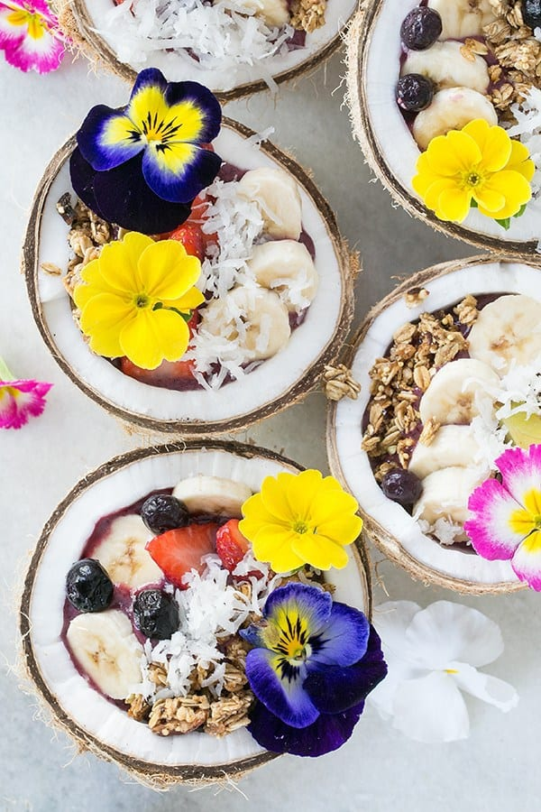 Four coconut acai bowls filled with toppings.