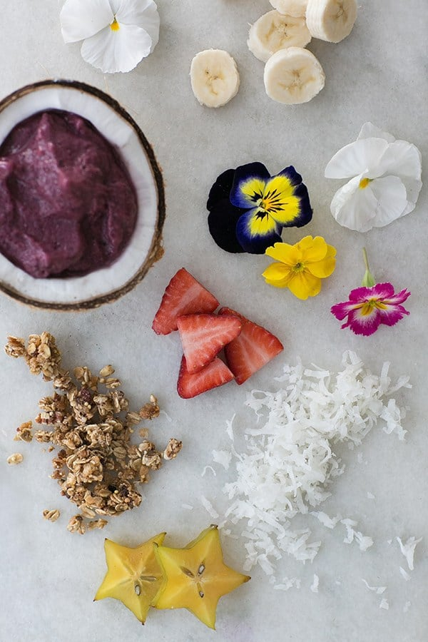 Sliced bananas, edible flowers, strawberries and granola on a marble table with an acai bowl.