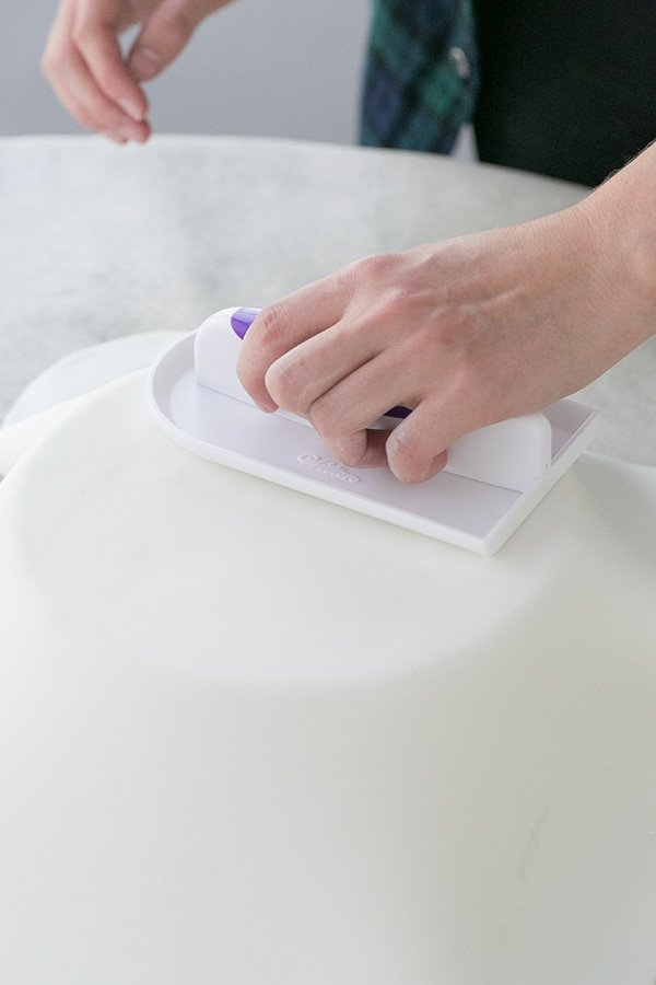 Fondant being smoothed over the cake