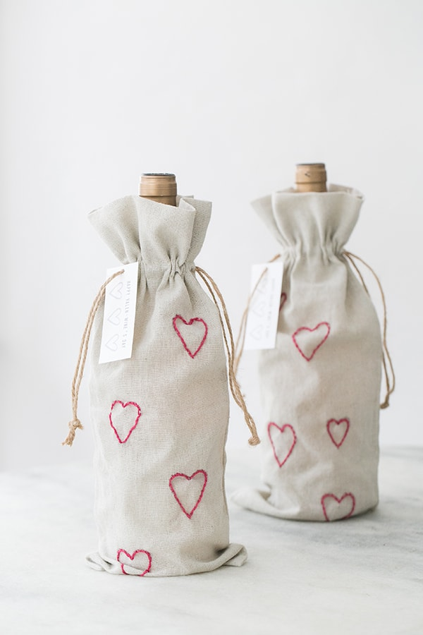 Two bottles of wine inside DIY Valentine's Day wine bags with embroidery pint hearts.