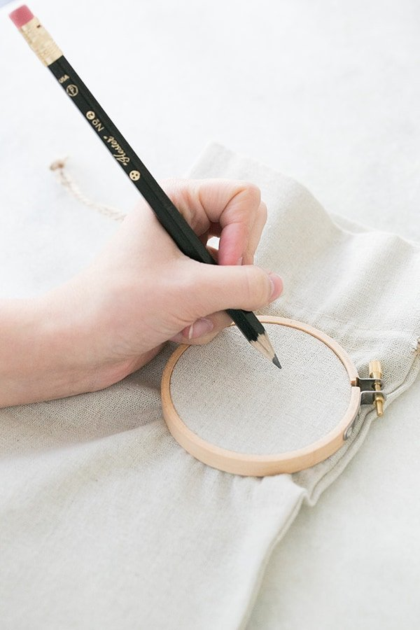 hand writing on a wine bag with an embroidery hoop to make a Valentine's day craft.