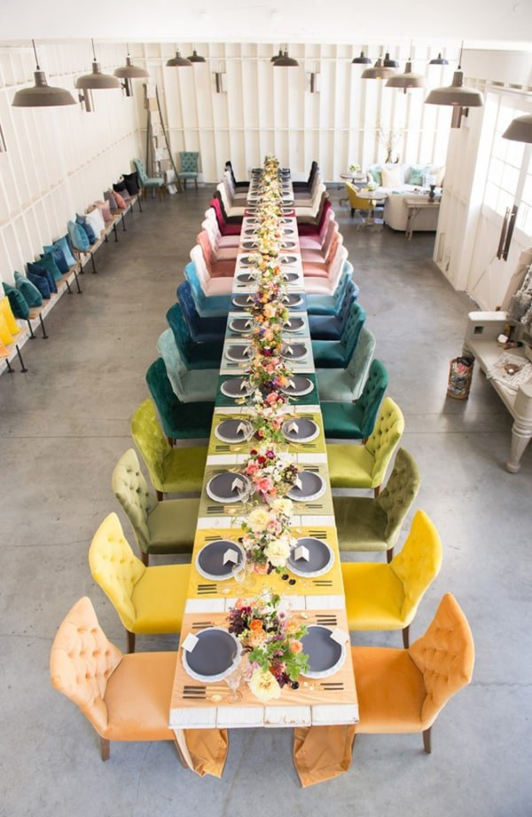 Overhead of colorful chairs going down the center of a table.