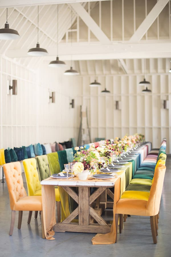 Long table inside a barn with colorful chairs and flowers.