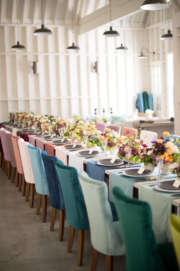 Colorful chairs and a table with flowers.