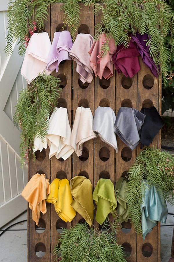 Colorful table linens in a wooden wine rack.