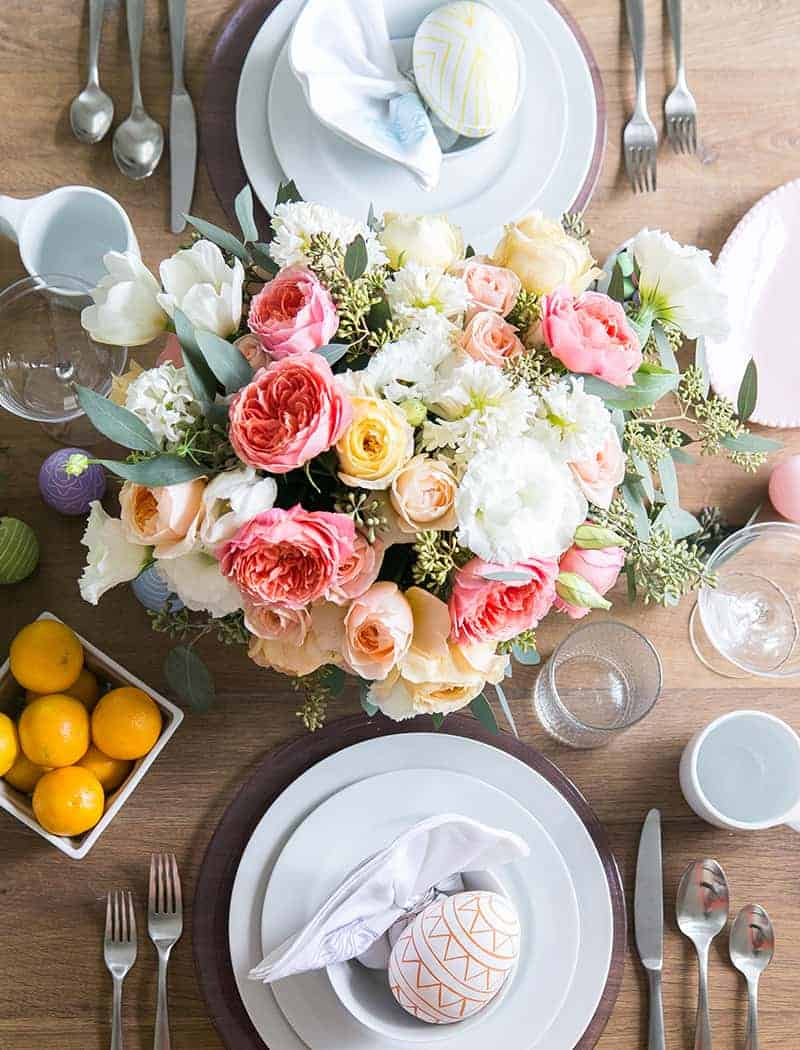 Easter table setting with flowers, dinnerware and Easter eggs