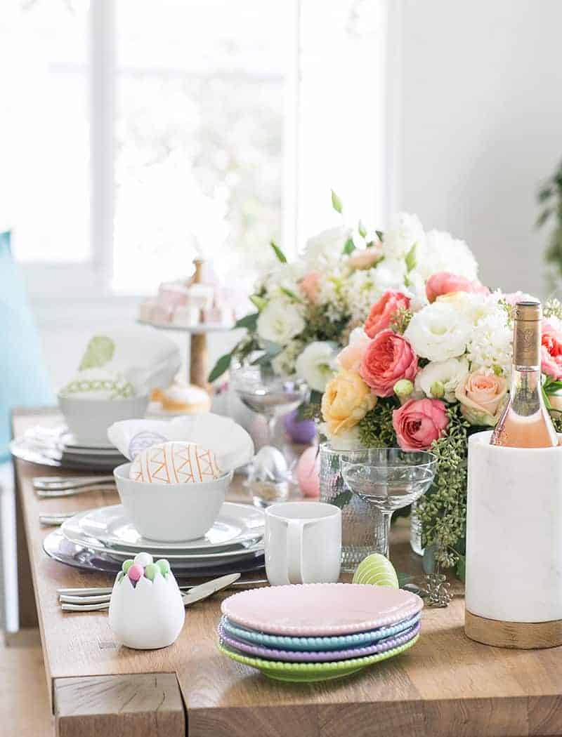 An easter table setting with flowers, wine, egg shaped plates.