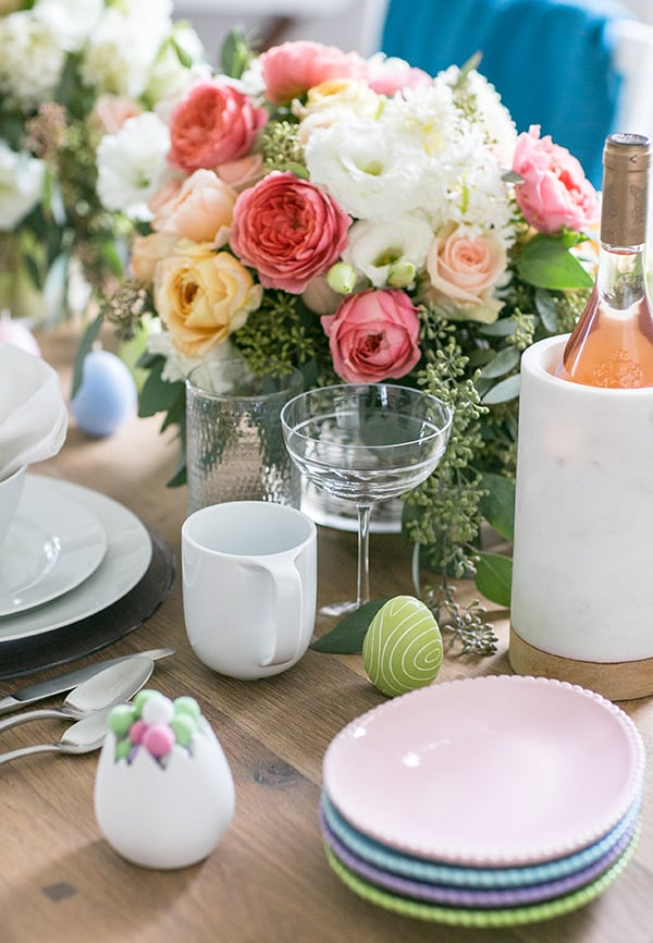 Easter brunch ideas on a table with flowers, wine, plates and candy.