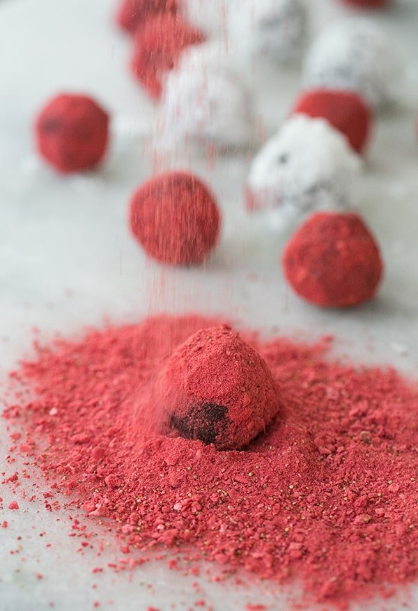 coconut truffles being dusted with strawberry dust