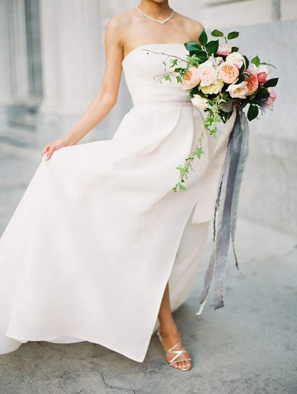 Bride in a white dress with bouquet of flowers.