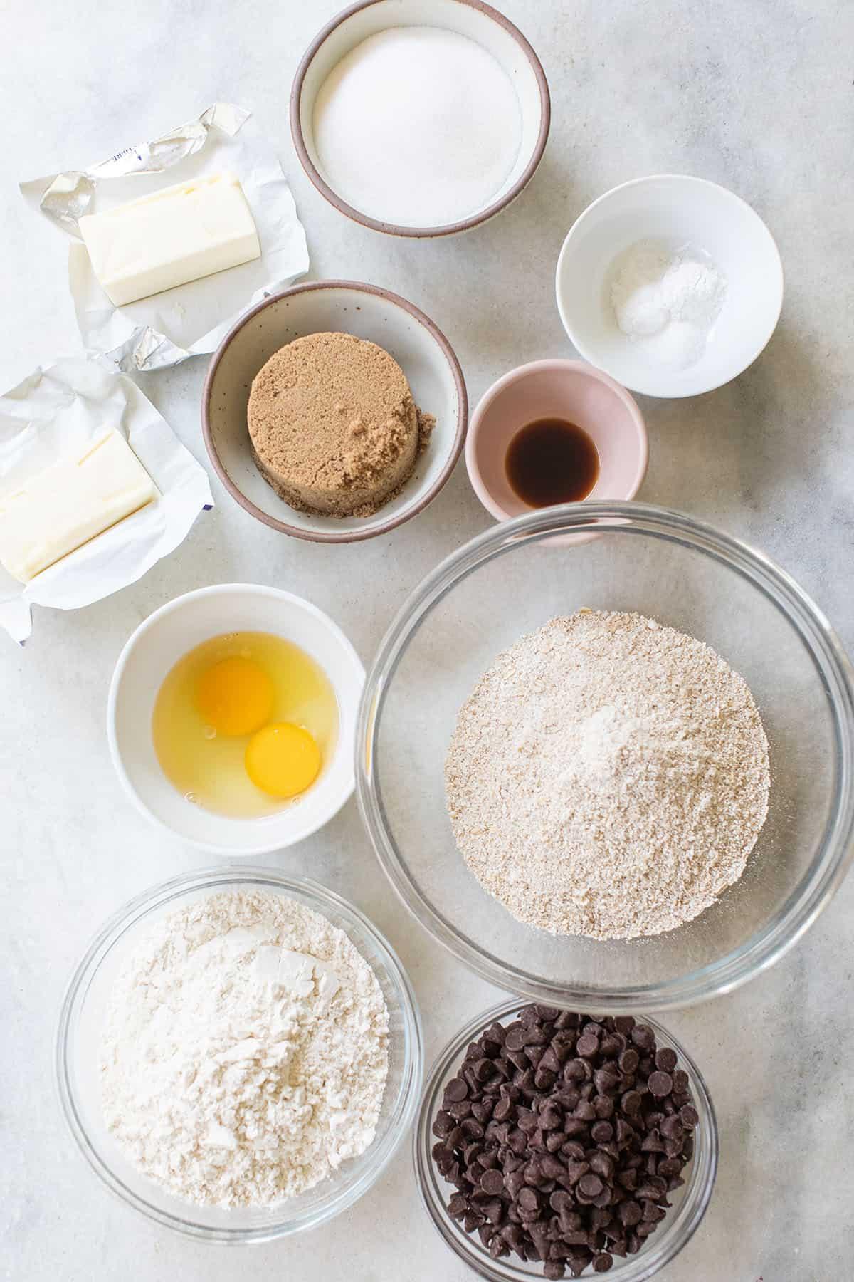 butter, sugar, brown sugar, eggs, oats, flour, vanilla extract, baking soda and powder in bowls.