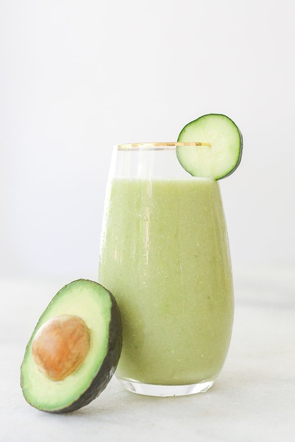 Frozen green cocktail in a tall glass with cucumber and avocado