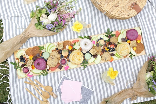 Board with treats on a picnic blanket