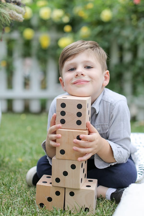 Little boy holding large dice at a picnic.