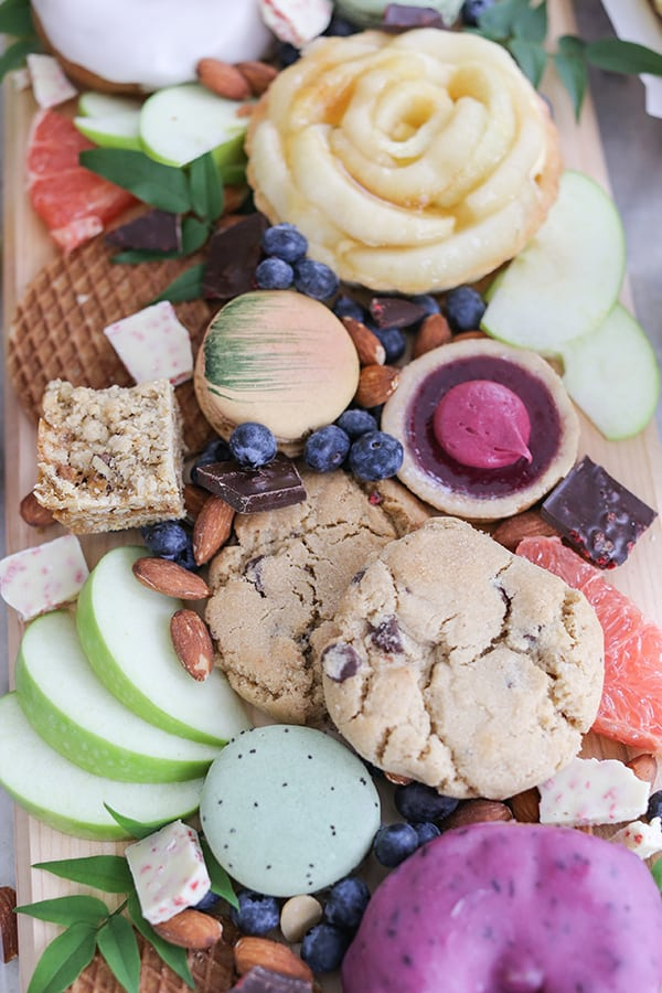 Cookies, apples, berries and bars on a wooden board.