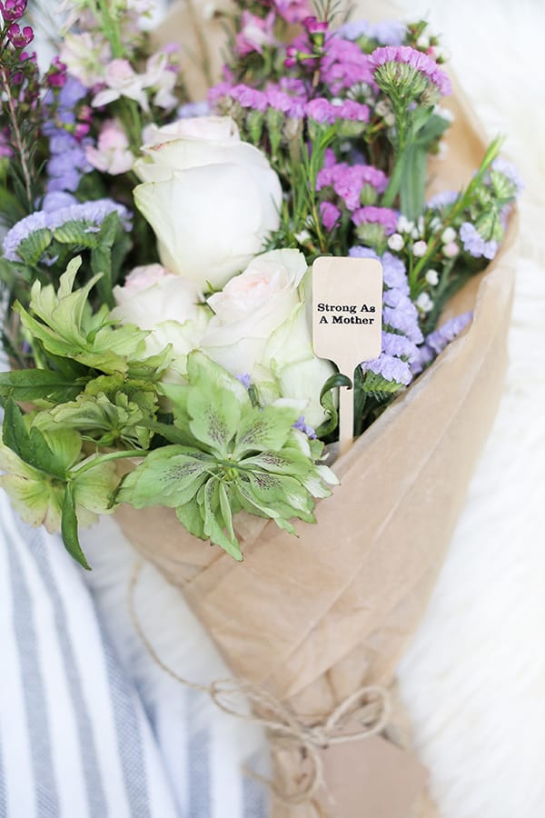Bouquet of flowers with a wooden sign that says strong as a mother.
