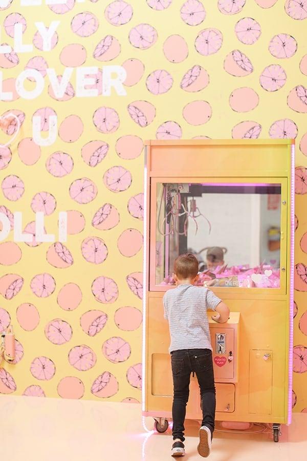 Little boy playing a vending machine with lemon wallpaper.