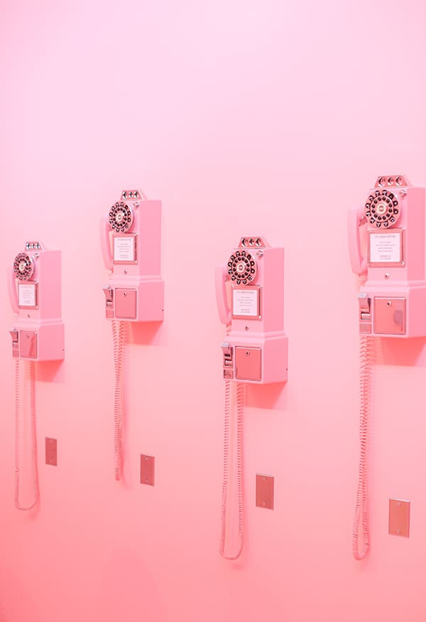 Pink telephones on a pink wall.